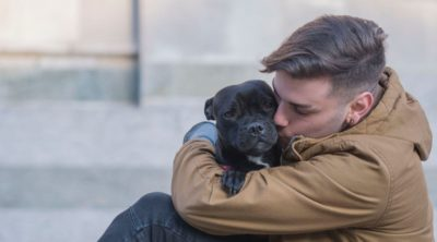 man hugging dog pet